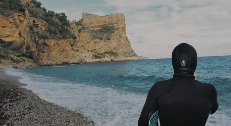 Man ready to surf wearing wetsuit hood