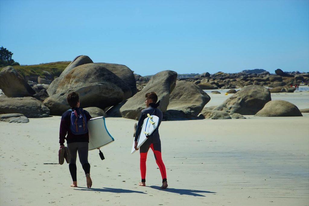 men carrying bodyboards